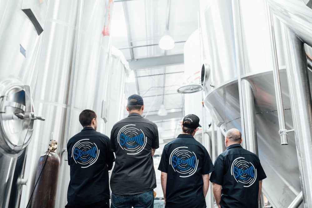 Seismic Brewing team with logos on their shirt backs